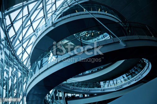 Looking up at a spiral walkway in City Hall beside the River Thames and Tower Bridge in London, UK.