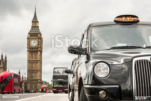 London's taxis and red buses front of big ben on a  cloudy day, selective focus