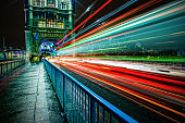 London double-decker bus light trails at Tower Bridge, UK.