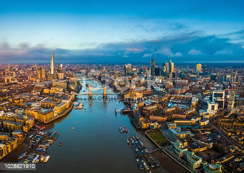 London, England - Panoramic aerial skyline view of London including Tower Bridge with red double-decker bus, Tower of London, skyscrapers of Bank District and other famous skyscrapers at golden hour