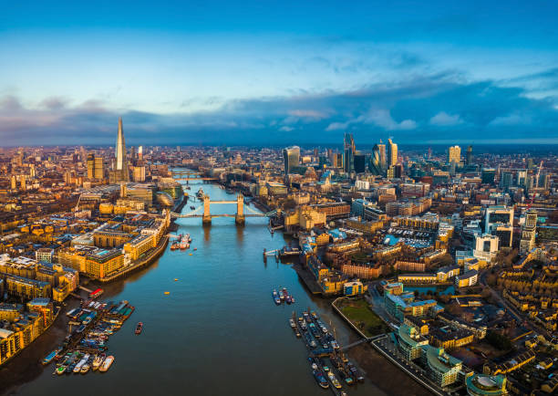 London, England - Panoramic aerial skyline view of London including Tower Bridge with red double-decker bus, Tower of London, skyscrapers of Bank District London, England - Panoramic aerial skyline view of London including Tower Bridge with red double-decker bus, Tower of London, skyscrapers of Bank District and other famous skyscrapers at golden hour london england stock pictures, royalty-free photos & images