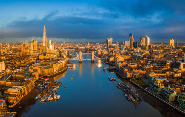 London, England - Panoramic aerial skyline view of London including iconic Tower Bridge with red double-decker bus, skyscrapers of Bank District stock photo