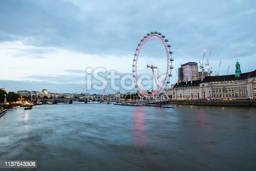 Beautiful London eye on Thames river at dusk, side view