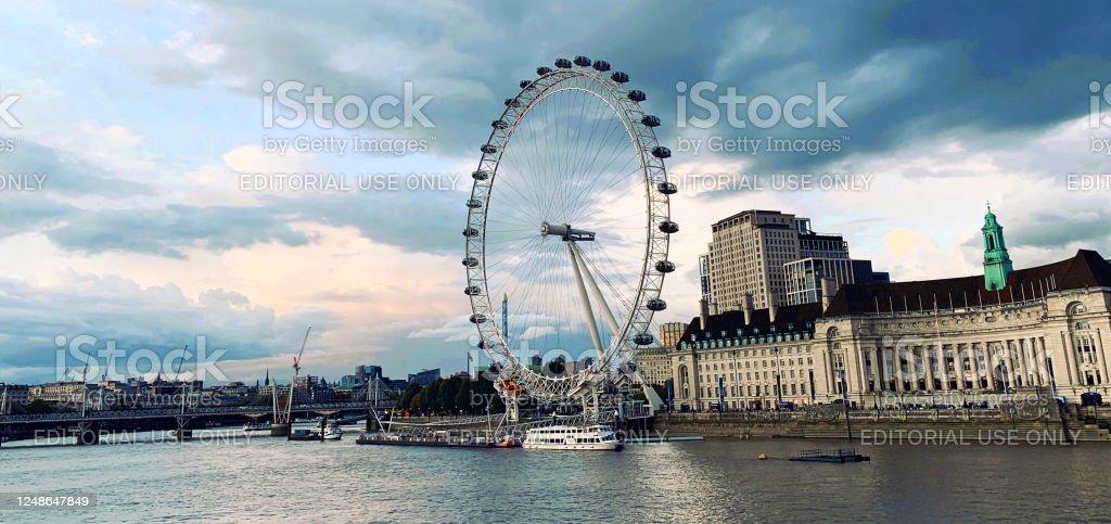 London Eye at sunset London Cityscape with symbolic ferris wheel London Eye on Thames river at sunset, United Kingdom. Architecture Stock Photo