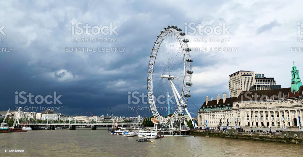 London Eye London Cityscape with symbolic ferris wheel London Eye on Thames river, minutes before the storm, United Kingdom. Architecture Stock Photo
