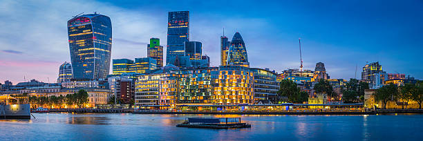 London futuristic skyscrapers glittering at sunset overlooking River Thames UK - foto stock