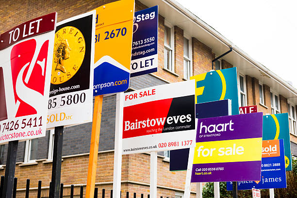 London Housing Market London, England, United Kingdom - 11 February 2015: Large group of estate agent boards from a variety of agencies outside a housing development in Hackney an up and coming district of the UK capital city. house for sale stock pictures, royalty-free photos & images