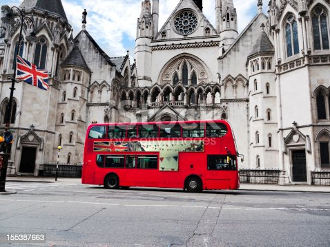 London bus with union jack flag in front of the Law Courts building. (Image on side of bus is the photographer's own).