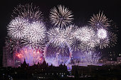 Midnight is celebrated along the River Thames in London with a spectacular and colourful  firework display. View over city rooftops