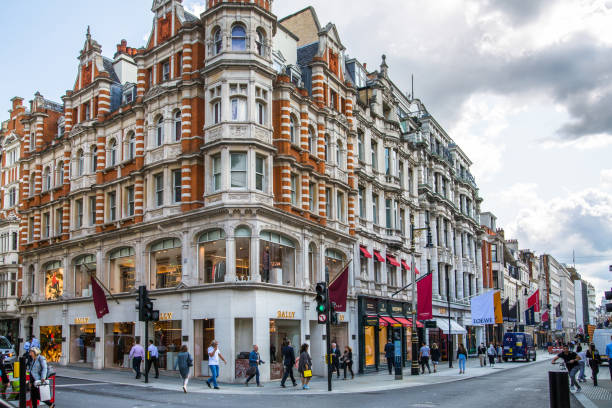 UK. London, Old Bond street view with flags of famous fashion houses. London, UK - August 13, 2019: Old Bond street view with flags of famous fashion houses. Bond Street is a major shopping street in the West End of London for luxury designer brands mayfair stock pictures, royalty-free photos & images