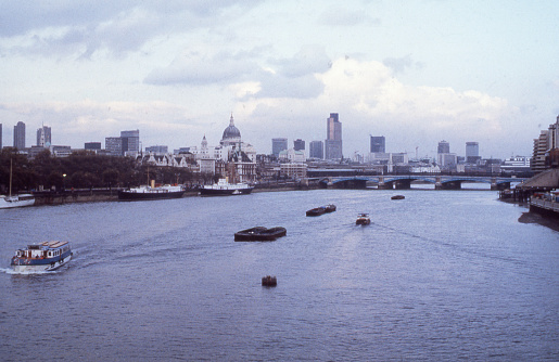 A partial view of the London Skyline facing eastward from the Waterloo Bridge highlights the importance of London's bustling river commerce. Figuring prominently among the numerous buildings is the dome of St. Paul's Cathedral, a popular tourist destination.