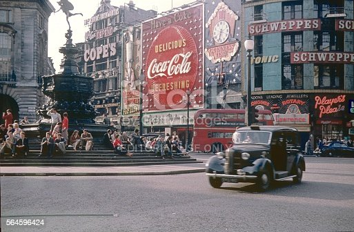 London,England,UK, Mai 22, 1968. The famous Piccadilly Circus to the Regant Street. Left the Shaftesbury Memorial Fountain. On the Steps at the Base sitting young People, Londoners and Tourists. They see the world go by on the busy square.