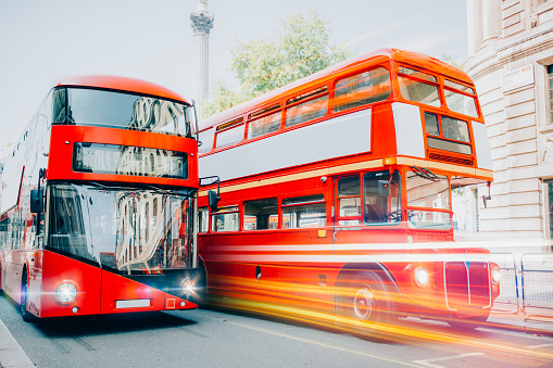 Red Buses New and Old in motion with light rails in London, United Kingdom