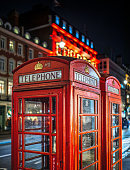 Two classic red telephone booth in front of an illuminated Christmas lights during night time in London, UK