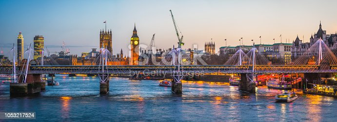 Panoramic view across the landmarks of central London, from the Southbank across the River Thames to the iconic towers of the Houses of Parliament and Big Ben illuminated against the blue dusk sky of the UK's vibrant capital city.