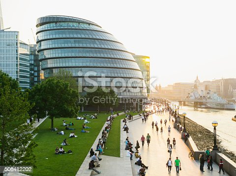 Tourists  and locals walking on the riverbank of Thames. City hall on the left.