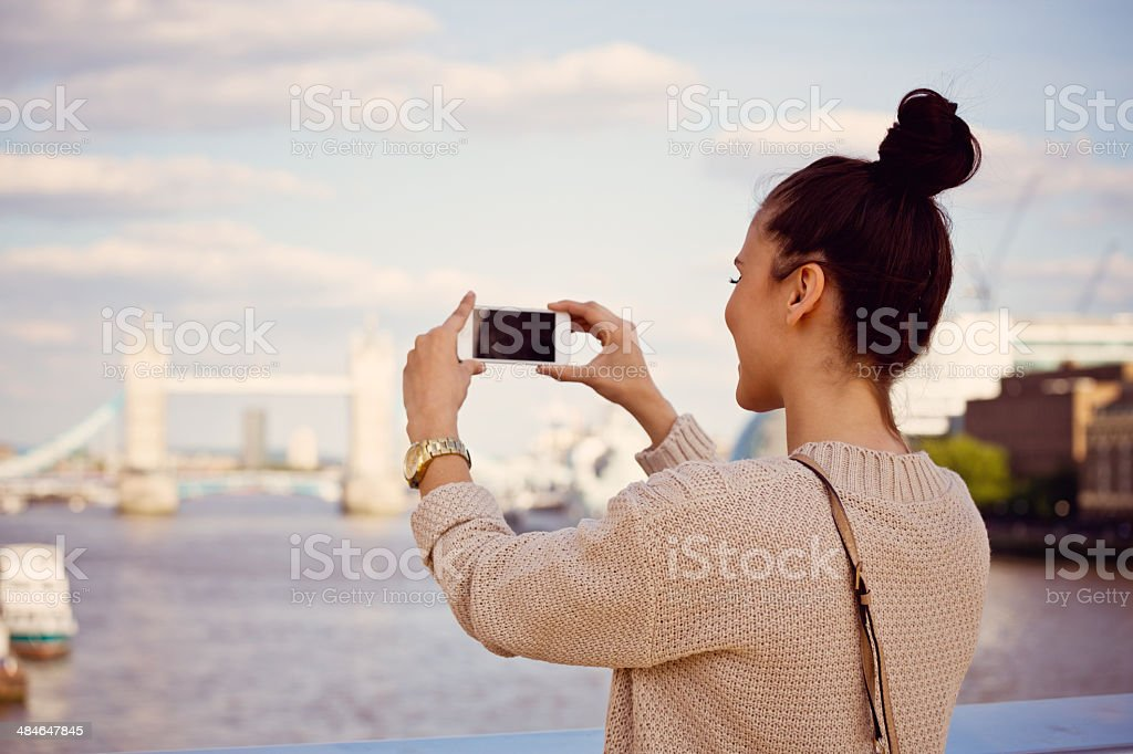 London sightseeing Back view of female tourist taking picture of Tower Brigde in London using her smart phone. 20-24 Years Stock Photo