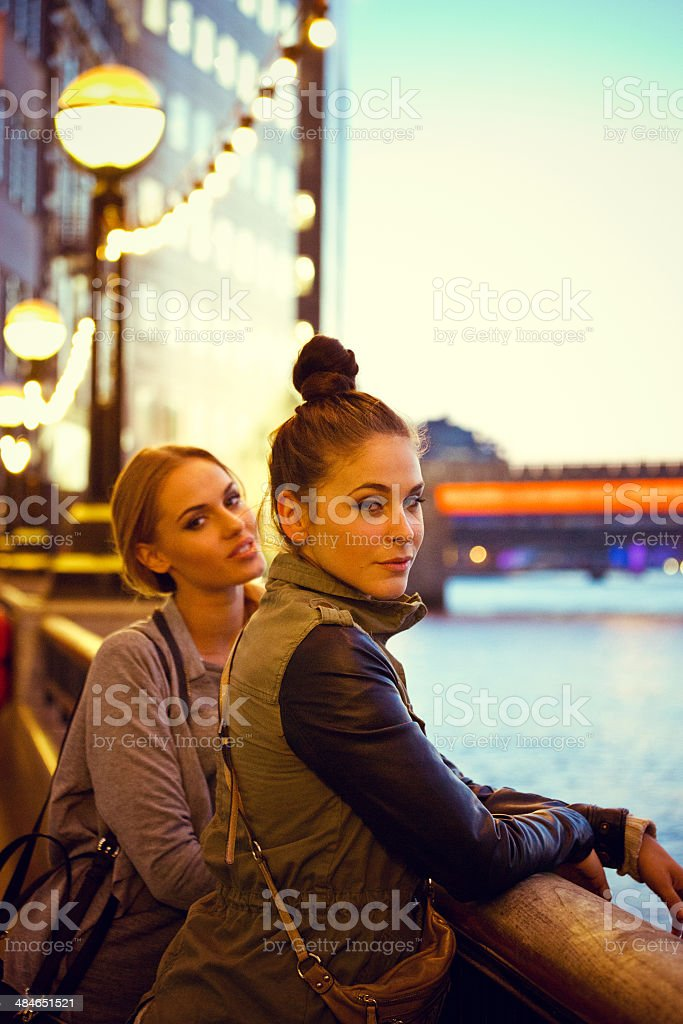 London sightseeing Outdoor portrait of two young women standing at Thames River at the sunset. 20-24 Years Stock Photo
