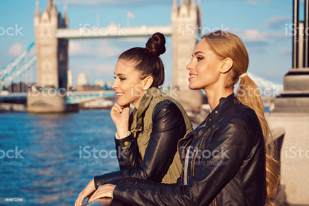 London sightseeing Side view of two pensive young women looking at Thames River with Tower Brigde in the background. 20-24 Years Stock Photo