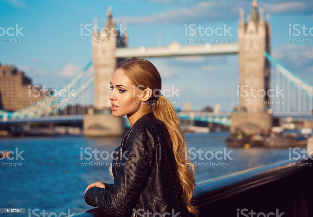 London sightseeing Side view of pensive young woman looking at Thames River with Tower Brigde in the background. 20-24 Years Stock Photo