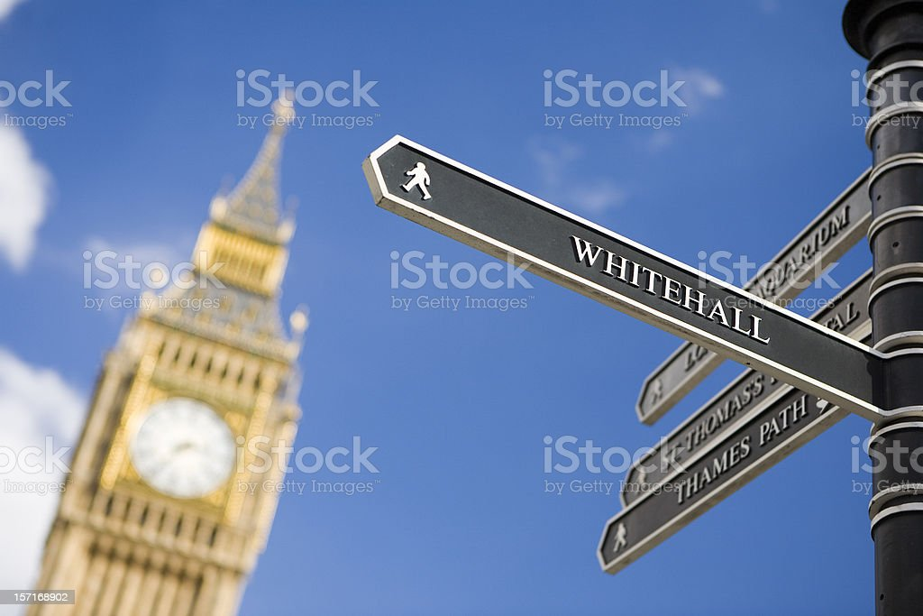 London sign directing towards Whitehall with Big Ben in background stock photo