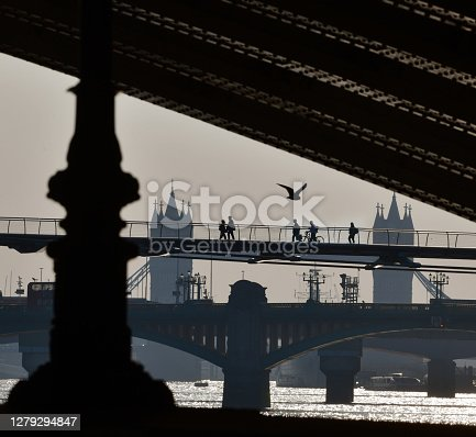 London bridges with distant figures in silhouette crossing the River Thames footbridge. View from the Embankment under and framing Blackfriars Railway bridge arch