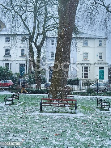Camden, London, January 2021 - Landscape image of a small London park under snowfall, snowflakes in the air and white already accumulating under foot. In the foreground, a collection of benches stand around an established tree, as a person walks along a path behind the tree in the mid-ground. Background shows the houses surrounding the garden under a white winter sky.