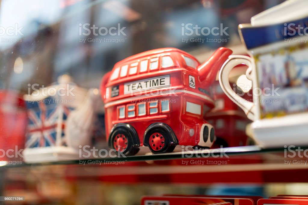 A London souvenir shop displaying British souvenirs including a classic British red double decker bus tea pot celebrating a royal wedding in the UK stock photo