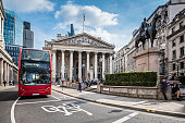 Bus waiting in front of the London Stock Exchange on a sunny day.