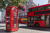 red phone booth with colored flowers and red bus, england, great britain, london