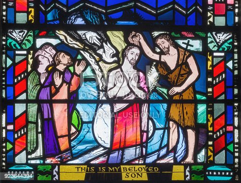 istock London - The Baptism of Jesus scene on the stained glass in church St Etheldreda by Charles Blakeman (1953 - 1953). 923644394
