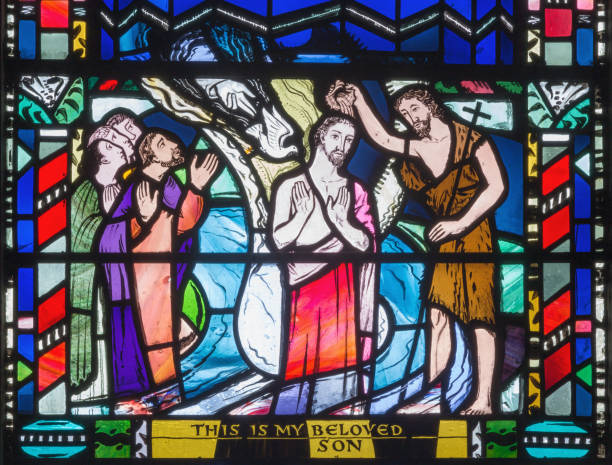London - The Baptism of Jesus scene on the stained glass in church St Etheldreda by Charles Blakeman (1953 - 1953). stock photo