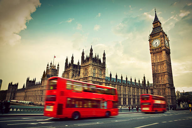 london, the uk. red bus in motion and big ben - big ben stock photos and pictures