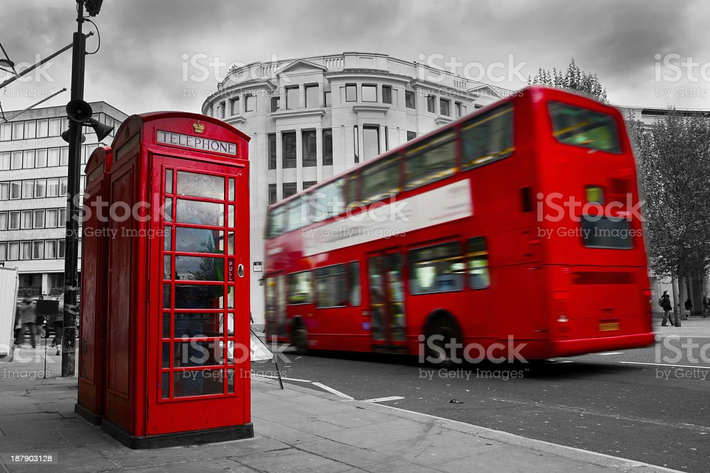 London, the UK. Red phone booth and bus in motion stock photo