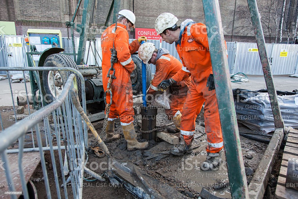 London three Workmen and a borehole stock photo