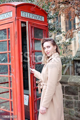 London tourist travel beautiful woman posing near red telephone box. Europe travel destination. Caucasian girl turning looking to the camera.