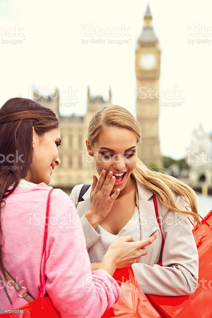 London tourists Two happy young women looking at smart phone with Big Ben in the background. 20-24 Years Stock Photo
