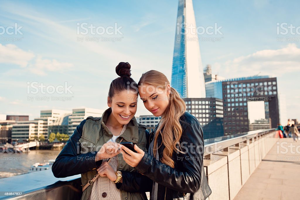London tourists Outdoor portrait of two young women using the smart phone with The Shard Tower in the background. 20-24 Years Stock Photo