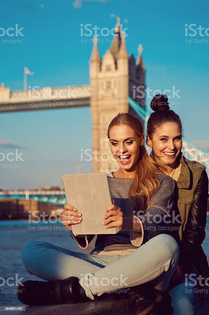 London Tourists Outdoor portrait of two happy young women taking a self picture using a digital tablet with Tower Brigde in the background. 20-24 Years Stock Photo