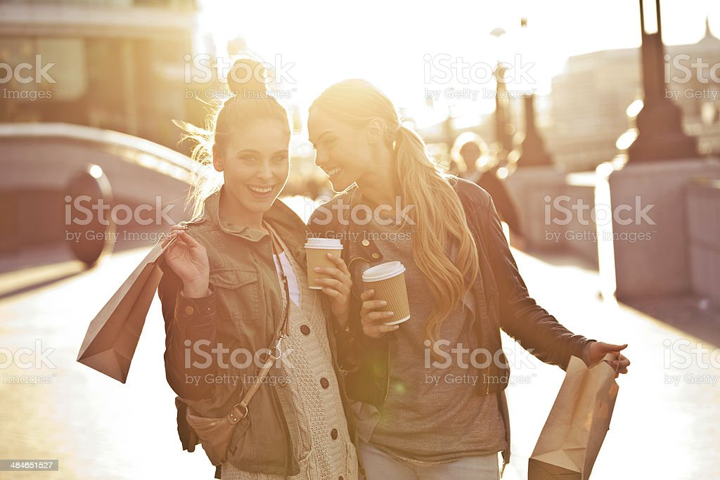 London tourists Outdoor portrait of two young happy women walking with take away coffee in hands at sunset. 20-24 Years Stock Photo