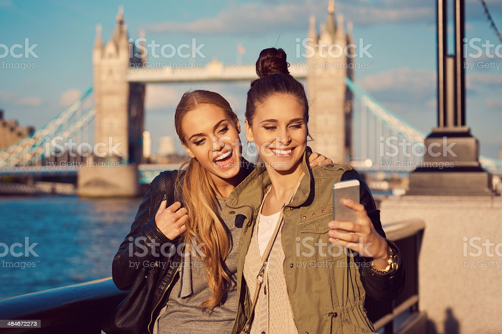 London tourists Outdoor portrait of two young women taking a self picutre using smart phone with Tower Brigde in the background. 20-24 Years Stock Photo