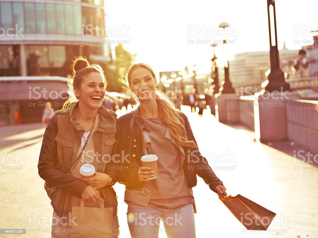 London tourists Outdoor portrait of two young happy women walking with take away coffee in hands. 20-24 Years Stock Photo