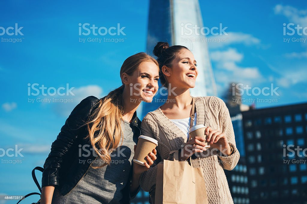 London tourists Outdoor portrait of two young happy women holding take away coffee in hands, looking away, with The Shard Tower in the background. 20-24 Years Stock Photo