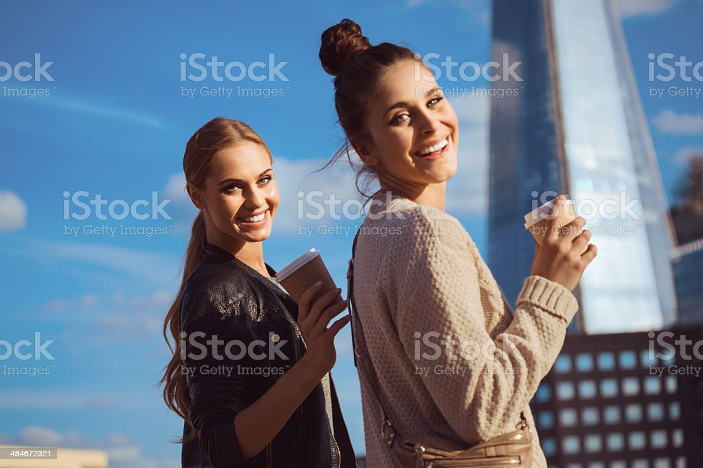 London tourists Outdoor portrait of two young happy women holding take away coffee in hands, smiling at camera with The Shard Tower in the background. 20-24 Years Stock Photo