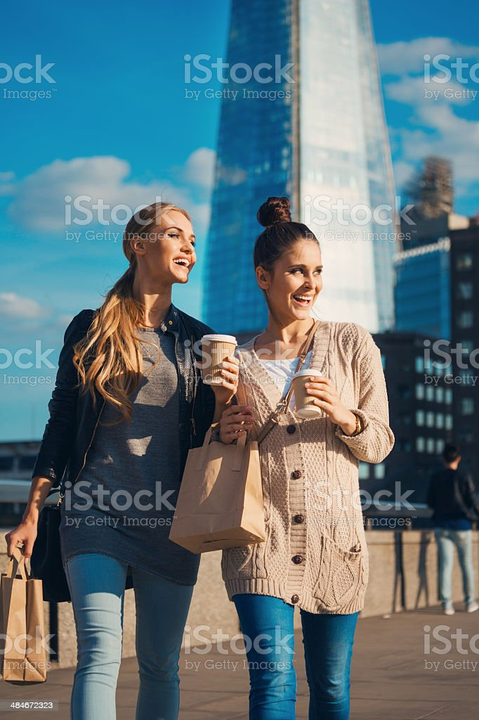 London tourists Outdoor portrait of two young happy women walking with take away food and coffee in hands, with The Shard Tower in the background. 20-24 Years Stock Photo