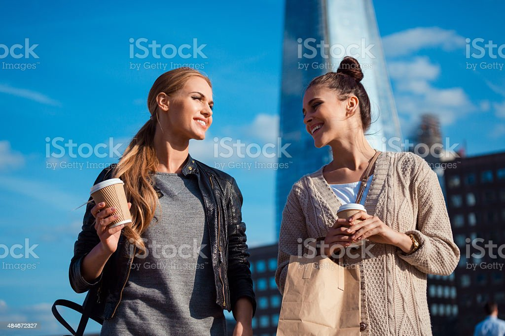 London tourists Outdoor portrait of two young happy women holding take away coffee in hands, with The Shard Tower in the background. 20-24 Years Stock Photo