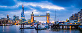 Panoramic view across the River Thames to the historic span of Tower Bridge illuminated against the blue dusk sky overlooked by the futuristic glass spire of The Shard in the heart of London, Britain's vibrant capital city. ProPhoto RGB profile for maximum color fidelity and gamut.