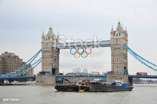 London, UK - August 15, 2012: London - View of Tower Bridge with the giant Olympic Rings suspended to mark the 2012 Summer Olympic games in London. Tour bus drives on London Bridge and boats cruise on river Thames.