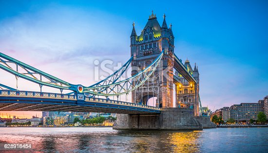 Summer sunset skies above the iconic span of Tower Bridge above the slow moving waters of the River Thames in the heart of London, Britain's vibrant capital city.