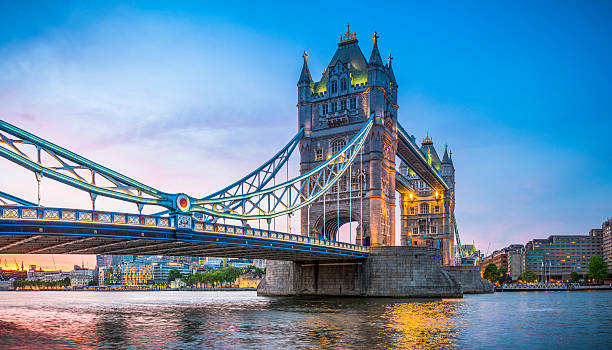 london tower bridge illuminated at sunset over river thames panorama - london england stock photos and pictures